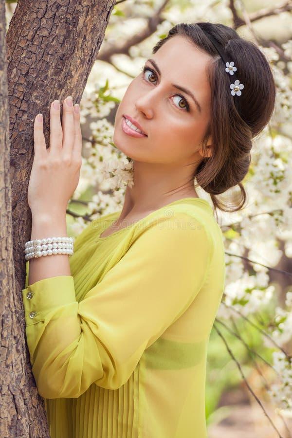 Πορτρέτο της νέας γυναίκας στο ανθίζοντας δέντρο την άνοιξη στοκ εικόνες
