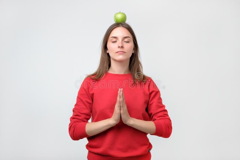 Πορτρέτο της νέας γυναίκας στο κόκκινο πουλόβερ που στέκεται με το πράσινο μήλο σε επικεφαλής και που στοκ φωτογραφία με δικαίωμα ελεύθερης χρήσης