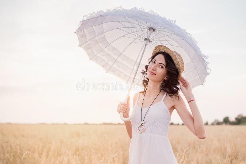 Πορτρέτο της νέας γυναίκας brunette στο καπέλο αχύρου στον τομέα σίτου με την άσπρη ομπρέλα στοκ φωτογραφία με δικαίωμα ελεύθερης χρήσης