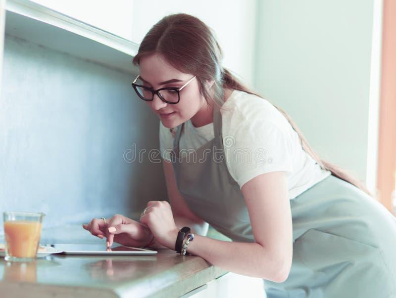 Πορτρέτο της νέας ελκυστικής καυκάσιας νοικοκυράς brunette στην κουζίνα Πρωί με το PC φλιτζανιών του καφέ και ταμπλετών στοκ φωτογραφία με δικαίωμα ελεύθερης χρήσης