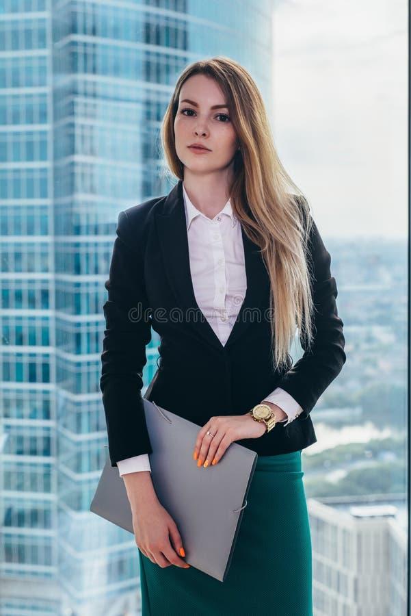 Πορτρέτο της νέας επιτυχούς επιχειρηματία που στέκεται στο γραφείο της ενάντια στο παράθυρο με μια άποψη σχετικά με τα εμπορικά κ στοκ φωτογραφία με δικαίωμα ελεύθερης χρήσης