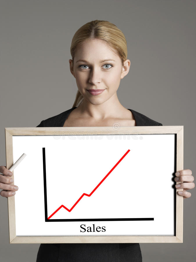 Πορτρέτο της νέας επιχειρηματία που παρουσιάζει γραφική παράσταση πωλήσεων στο γκρίζο κλίμα στοκ φωτογραφία με δικαίωμα ελεύθερης χρήσης