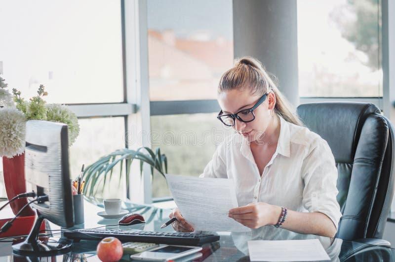 Πορτρέτο της νέας επιχειρησιακής κυρίας στα γυαλιά που κάθεται στο workpl της στοκ φωτογραφίες