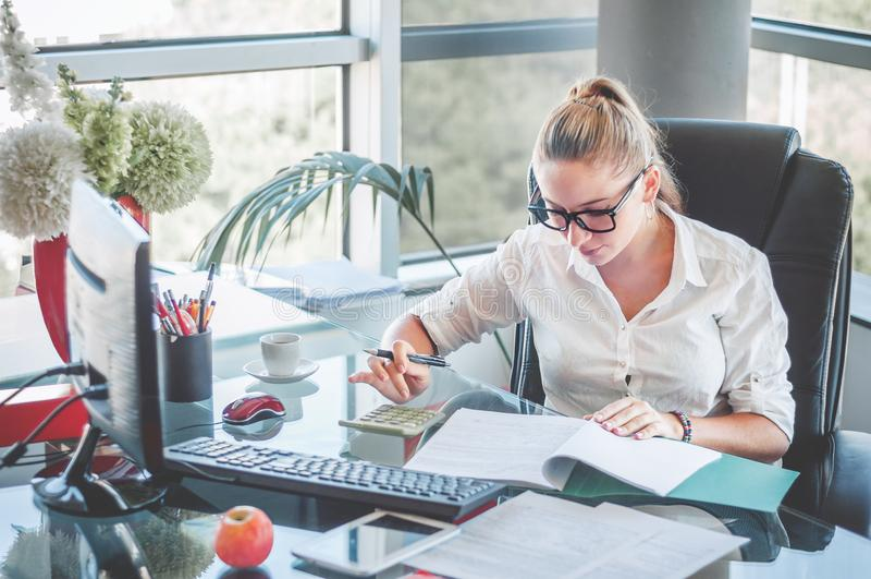 Πορτρέτο της νέας επιχειρησιακής κυρίας στα γυαλιά που κάθεται στο workpl της στοκ φωτογραφία με δικαίωμα ελεύθερης χρήσης