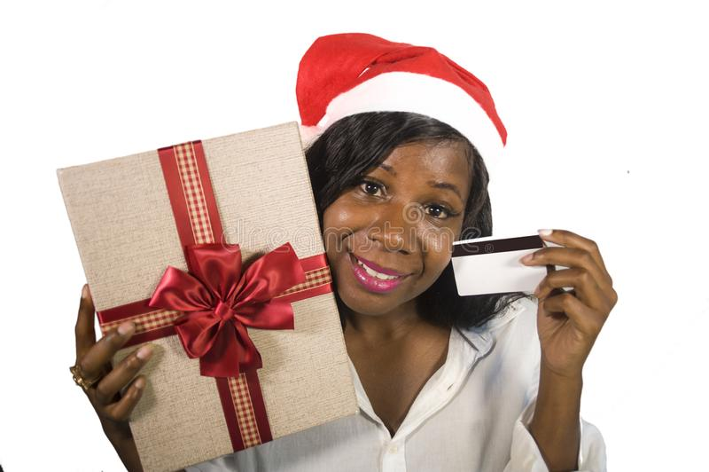 Πορτρέτο της νέας ευτυχούς και όμορφης αμερικανικής γυναίκας μαύρων Αφρικανών στο καπέλο Άγιου Βασίλη που κρατά το παρόν κιβώτιο  στοκ φωτογραφίες με δικαίωμα ελεύθερης χρήσης