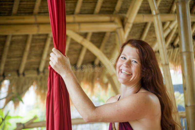 Πορτρέτο της νέας ευτυχούς και όμορφης κόκκινης γυναίκας τρίχας στο εναέριο χαμόγελο υφάσματος μεταξιού εκμετάλλευσης χορού aero  στοκ εικόνες