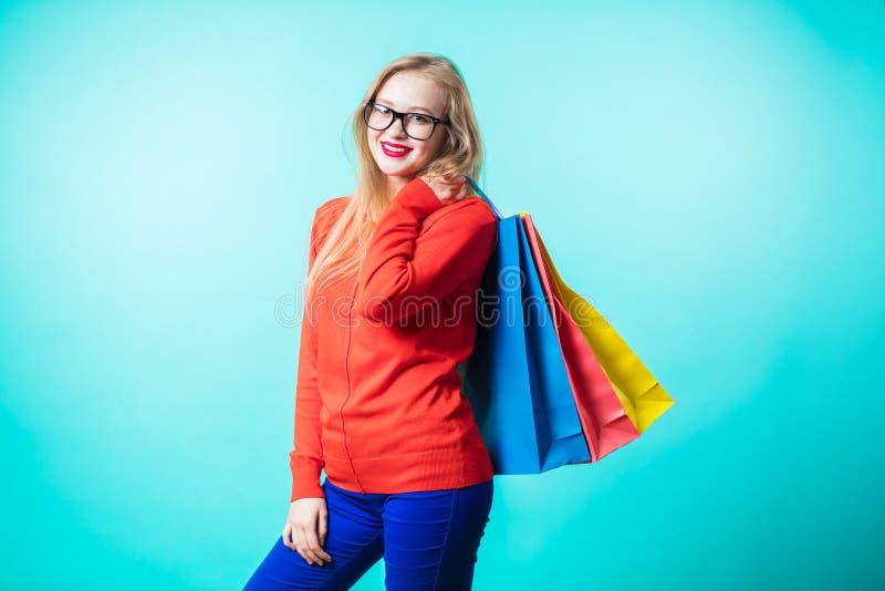 Πορτρέτο της νέας ευτυχούς χαμογελώντας γυναίκας με τις τσάντες αγορών στοκ φωτογραφία