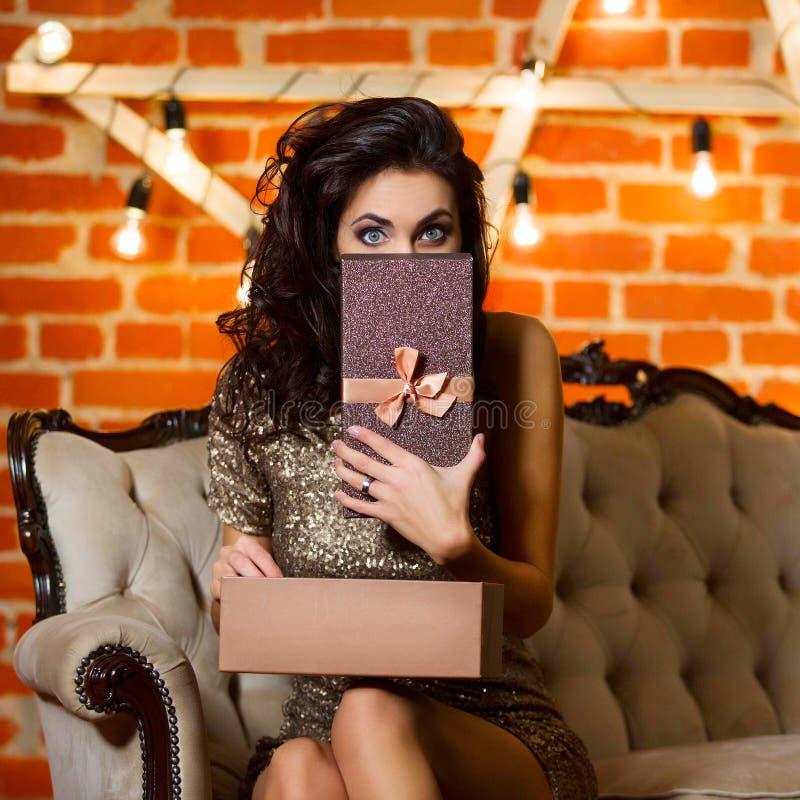 Πορτρέτο της νέας ευτυχούς όμορφης γυναίκας στη χρυσή εκμετάλλευση φορεμάτων στοκ φωτογραφία