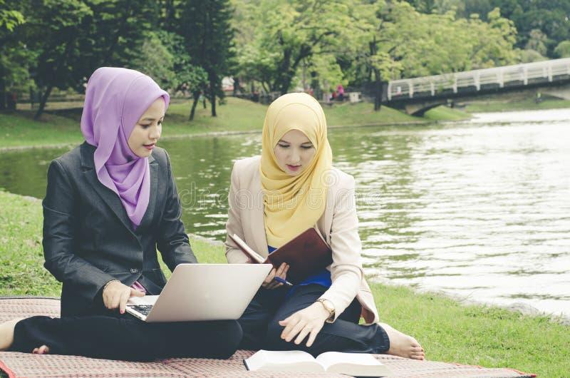 Πορτρέτο της νέας καλής ευχάριστης συνεδρίασης γυναικών μιγμάτων εθνικής στη χλόη στο θερινές πράσινο πάρκο και τη διοργάνωση μια στοκ εικόνες