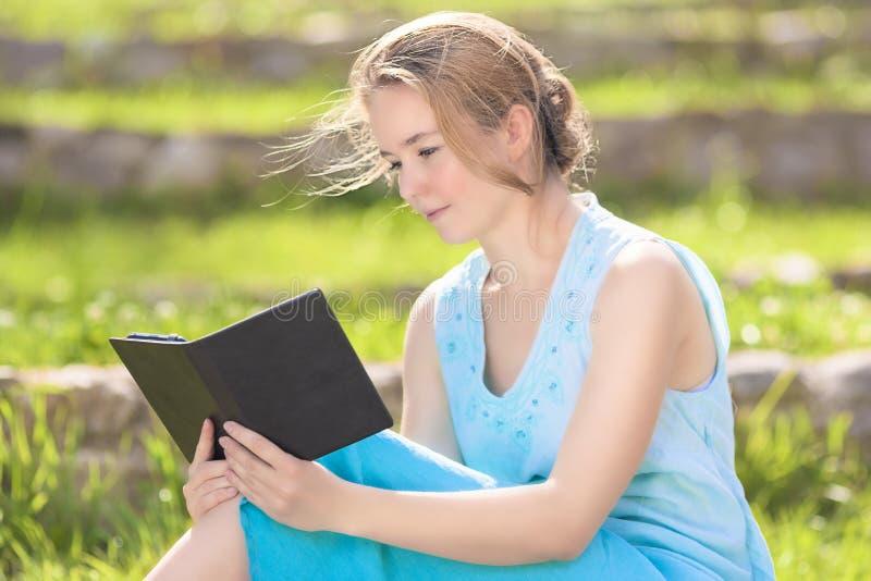 Πορτρέτο της νέας καυκάσιας ξανθής γυναίκας που διαβάζει το ψηφιακό eBook Ο στοκ εικόνες