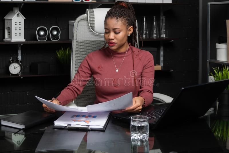 Πορτρέτο της νέας μαύρης επιχειρηματία που εργάζεται με τα διαγράμματα και τα διαγράμματα στο γραφείο στην αρχή στοκ εικόνες