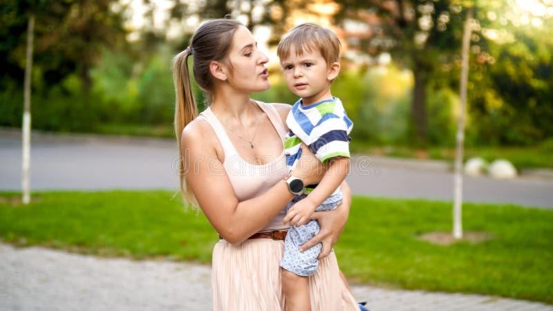 Πορτρέτο της νέας μητέρας που αγκαλιάζει 3 της χρονών λίγος γιος και που μιλά σε τον περπατώντας στο πάρκο στοκ εικόνα