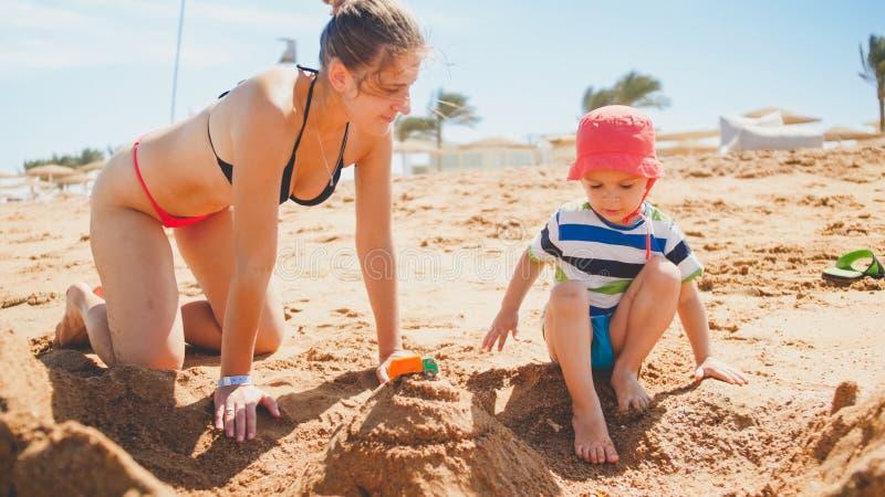 Πορτρέτο της νέας μητέρας που διδάσκει 3 χρονών κάστρα οικοδόμησης γιων μικρών παιδιών της από την άμμο στην παραλία θάλασσας r στοκ εικόνες