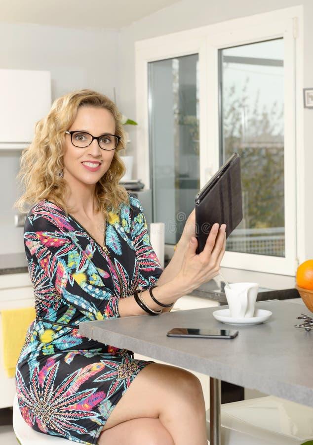 Πορτρέτο της νέας ξανθής γυναίκας στην κουζίνα με την ταμπλέτα comput στοκ φωτογραφία