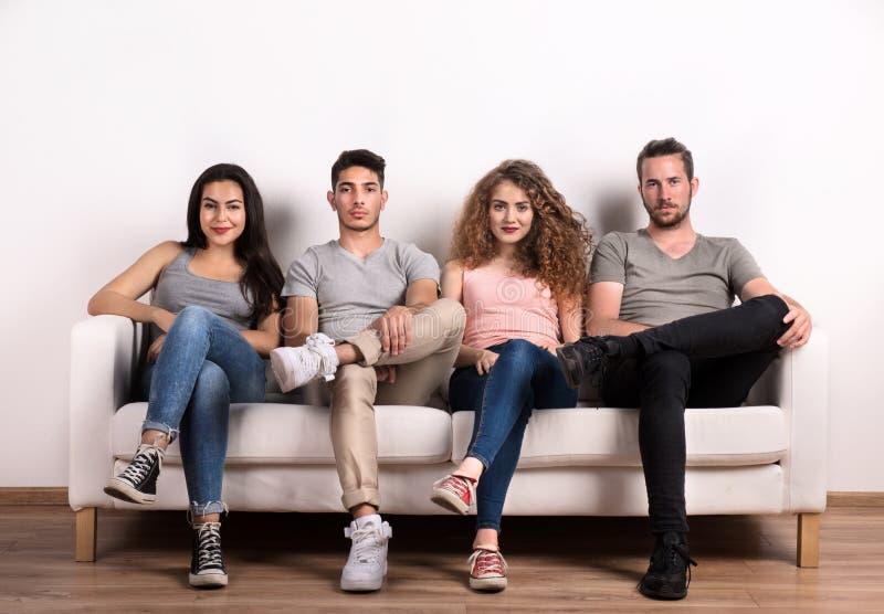 Πορτρέτο της νέας ομάδας φίλων που κάθονται σε έναν καναπέ σε ένα στούντιο στοκ φωτογραφίες