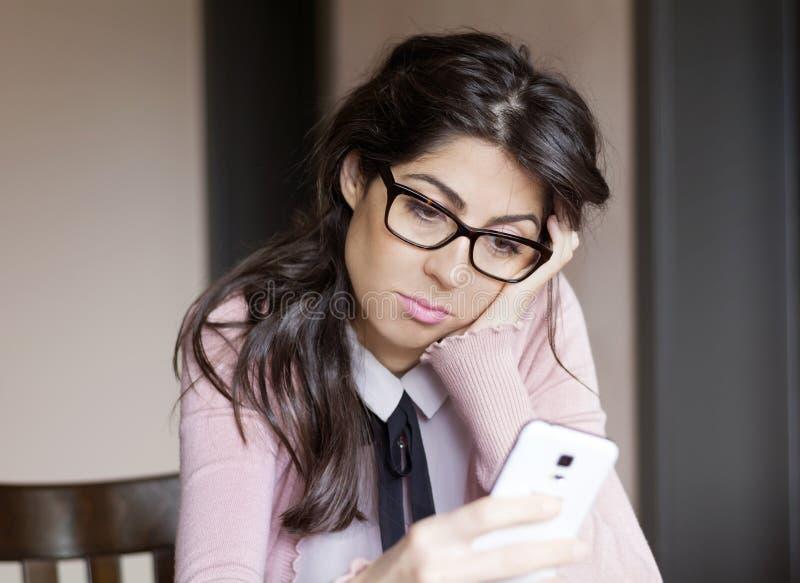 Πορτρέτο της νέας λυπημένης γυναίκας, που λαμβάνει τα κακά sms εσωτερικά στοκ εικόνες με δικαίωμα ελεύθερης χρήσης