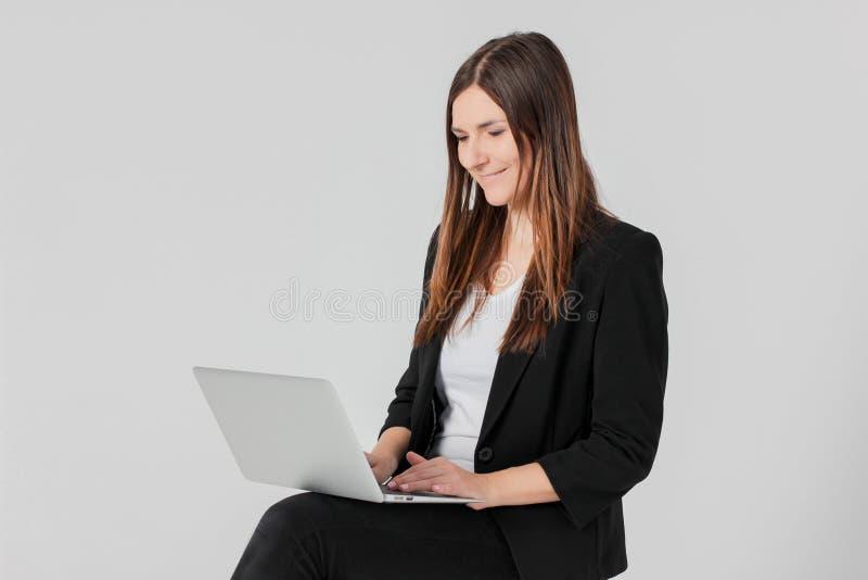 Πορτρέτο της νέας χαμογελώντας κυρίας γυναικών brunette στο επιχειρησιακό κοστούμι W στοκ φωτογραφία
