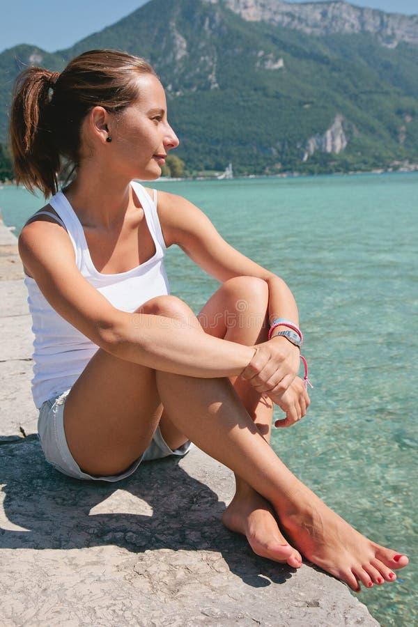 Πορτρέτο της νέας χαλάρωσης γυναικών κοντά στη θάλασσα. στοκ εικόνες