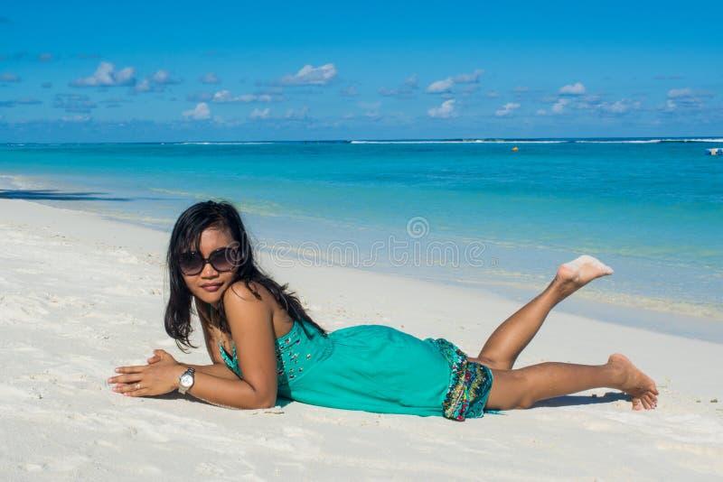 Πορτρέτο της νέας όμορφης ασιατικής τοποθέτησης κοριτσιών χαμόγελου στο στομάχι της στην παραλία στοκ εικόνες με δικαίωμα ελεύθερης χρήσης