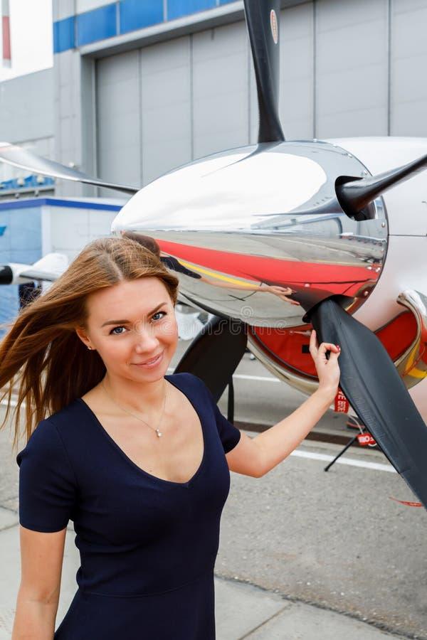 Πορτρέτο της νέας όμορφης γυναίκας κοντά fairing χρωμίου ενός προωστήρα του επιχειρησιακού αεριωθούμενου αεροπλάνου στοκ εικόνα