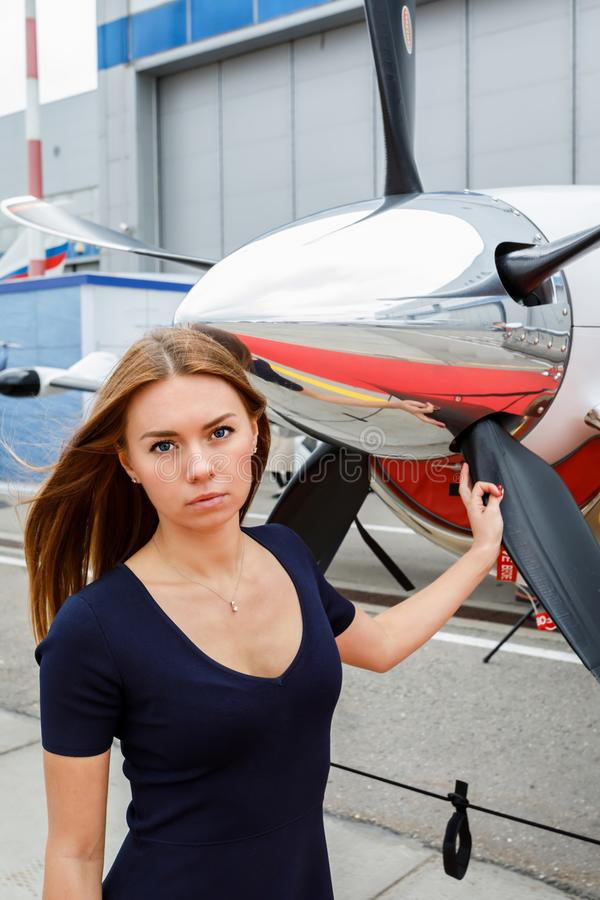 Πορτρέτο της νέας όμορφης γυναίκας κοντά fairing χρωμίου ενός προωστήρα του επιχειρησιακού αεριωθούμενου αεροπλάνου στοκ φωτογραφίες