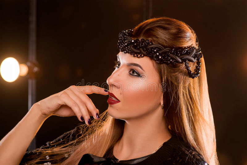 Πορτρέτο της νέας όμορφης γυναίκας με το χέρι σχεδόν το στόμα της στοκ εικόνα