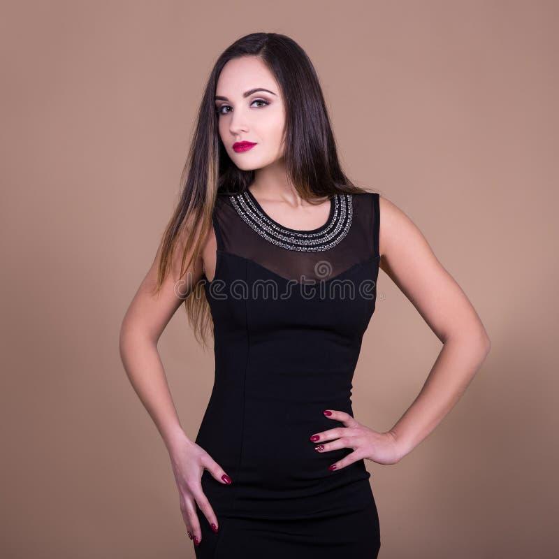 Πορτρέτο της νέας όμορφης γυναίκας στο μαύρο φόρεμα πέρα από την μπεζ πλάτη στοκ εικόνα με δικαίωμα ελεύθερης χρήσης