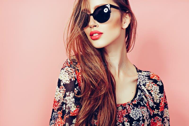 Πορτρέτο της νέας όμορφης λεπτής γυναίκας στο προκλητικό φόρεμα με τα αισθησιακά χείλια στο στούντιο που φορά τα γυαλιά ηλίου που στοκ φωτογραφίες με δικαίωμα ελεύθερης χρήσης