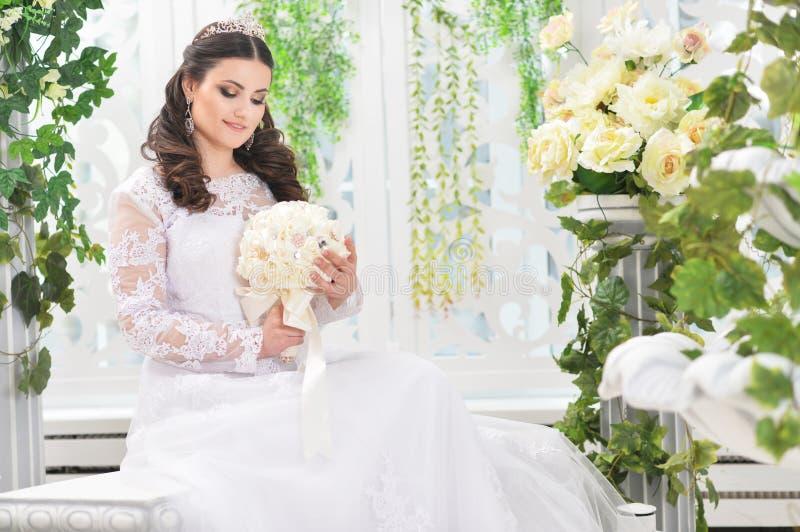 Πορτρέτο της νέας όμορφης νύφης στην άσπρη τοποθέτηση φορεμάτων στοκ φωτογραφία με δικαίωμα ελεύθερης χρήσης