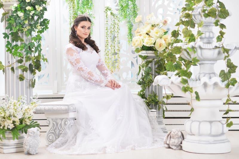 Πορτρέτο της νέας όμορφης νύφης στην άσπρη τοποθέτηση φορεμάτων στοκ εικόνες