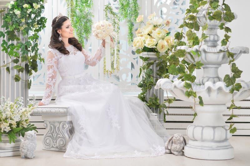 Πορτρέτο της νέας όμορφης νύφης στην άσπρη τοποθέτηση φορεμάτων στοκ εικόνα