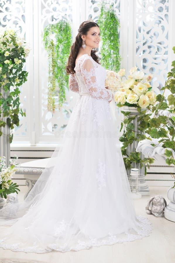 Πορτρέτο της νέας όμορφης νύφης στην άσπρη τοποθέτηση φορεμάτων στοκ φωτογραφίες