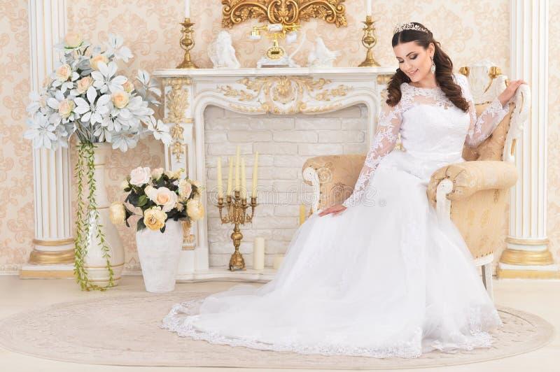 Πορτρέτο της νέας όμορφης νύφης στην άσπρη τοποθέτηση φορεμάτων στοκ φωτογραφία