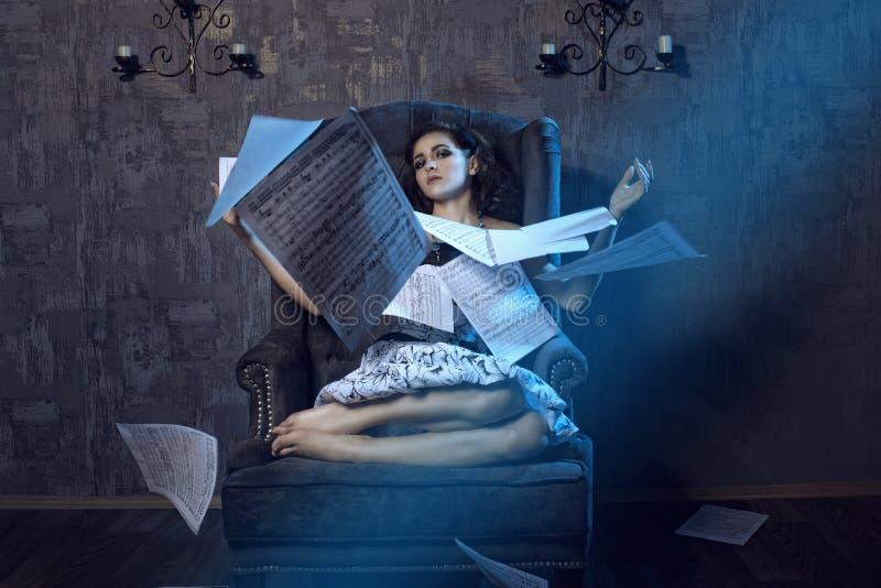 Πορτρέτο της νέας όμορφης συνεδρίασης μουσικών κοριτσιών στην γκρίζα πολυθρόνα βελούδου με τα πόδια της που πτυχώνονται και που ρ στοκ εικόνα με δικαίωμα ελεύθερης χρήσης