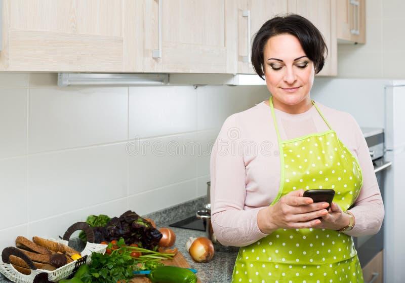 Πορτρέτο της νοικοκυράς στην ποδιά που λαμβάνει sms με τη συνταγή στοκ εικόνες