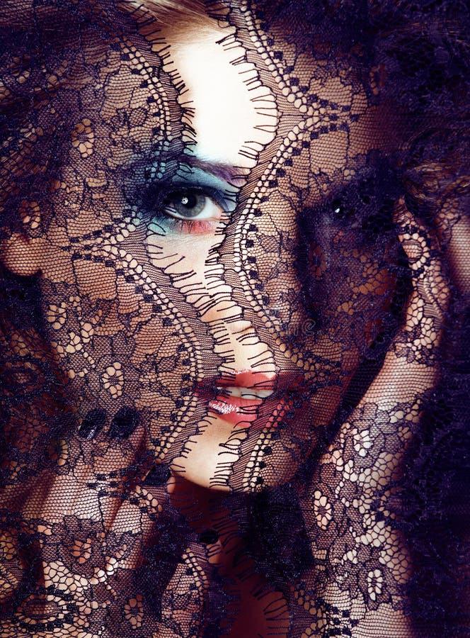 Πορτρέτο της ξανθής νέας γυναίκας ομορφιάς μέσω μαύρου στενού επάνω δαντελλών στοκ φωτογραφία