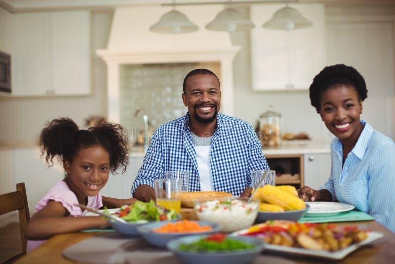 Πορτρέτο της οικογένειας που έχει το γεύμα ο πίνακας στο σπίτι στοκ φωτογραφίες