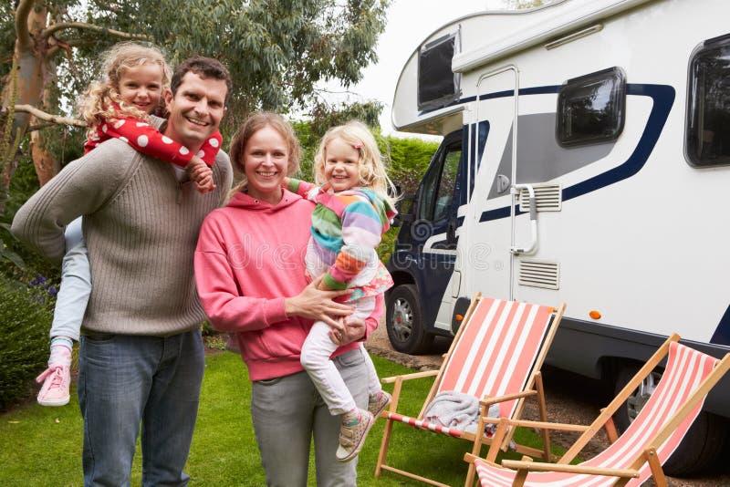 Πορτρέτο της οικογένειας που απολαμβάνει τις διακοπές στρατοπέδευσης στο φορτηγό τροχόσπιτων στοκ εικόνα