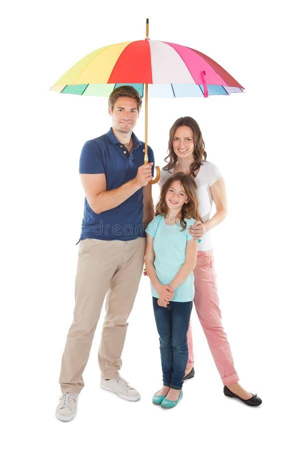 Πορτρέτο της οικογένειας που στέκεται μαζί κάτω από την ομπρέλα στοκ φωτογραφία