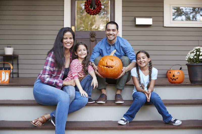 Πορτρέτο της οικογένειας που χαράζει την κολοκύθα αποκριών στα βήματα σπιτιών στοκ φωτογραφία με δικαίωμα ελεύθερης χρήσης