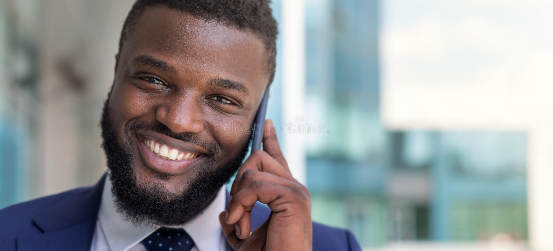 Πορτρέτο της ομιλίας επιχειρηματιών αφροαμερικάνων χαμόγελου τηλεφωνικώς υπαίθρια r στοκ εικόνα