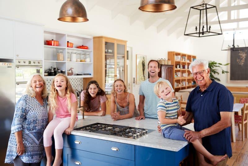 Πορτρέτο της πολυ οικογένειας παραγωγής που στέκεται γύρω από το νησί κουζινών από κοινού στοκ εικόνα