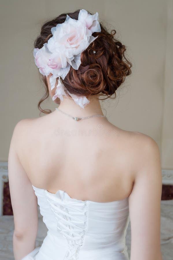 Πορτρέτο της πλάτης της νύφης στο άσπρο φόρεμα με το ύφος και το flo τρίχας στοκ εικόνα με δικαίωμα ελεύθερης χρήσης