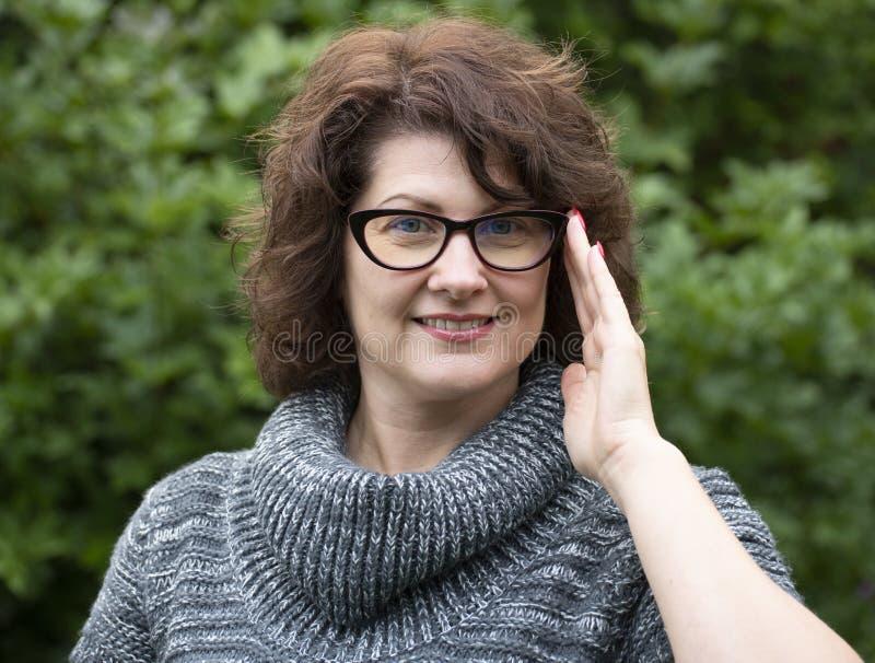 Πορτρέτο της σγουρής γυναίκας στα κόκκινα γυαλιά στη φύση στοκ εικόνες