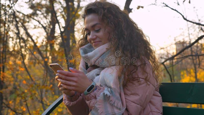 Πορτρέτο της σγουρός-μαλλιαρής καυκάσιας συνεδρίασης κοριτσιών στον πάγκο και της προσοχής πρόθυμα στο smartphone στο φθινοπωρινό στοκ εικόνες