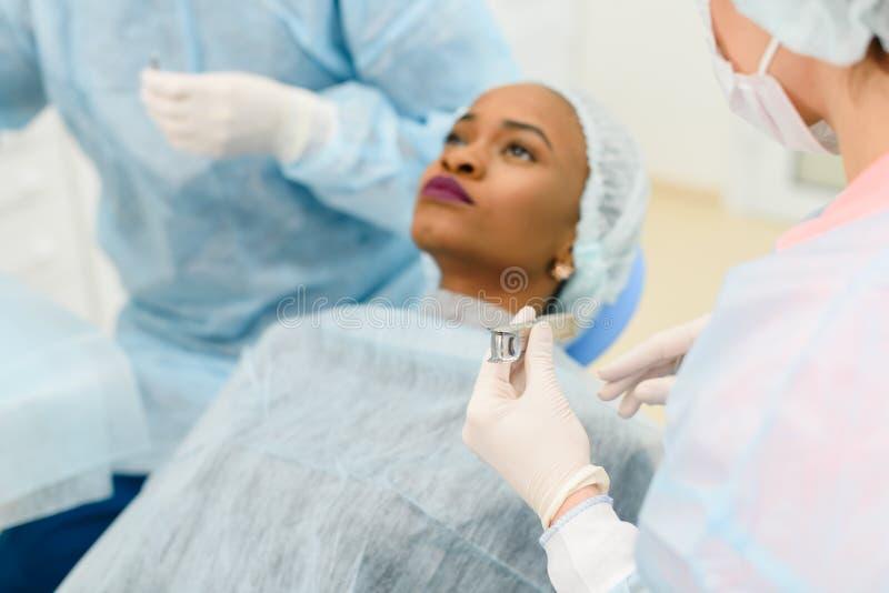 Πορτρέτο της σοβαρής μαύρης νέας γυναίκας που περιμένει έναν οδοντικό διαγωνισμό στοκ εικόνα