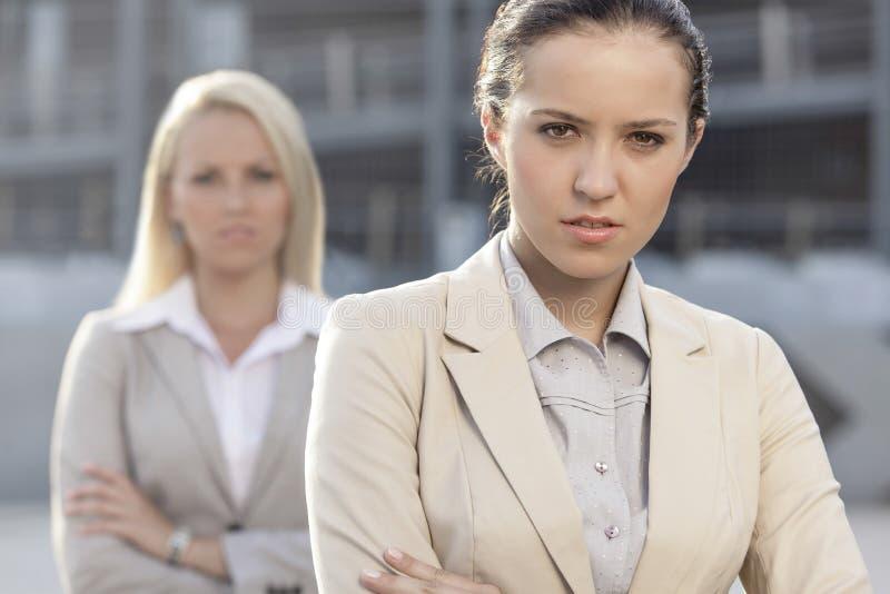 Πορτρέτο της σοβαρής νέας επιχειρηματία με τη γυναίκα συνάδελφος στο υπόβαθρο στοκ εικόνα