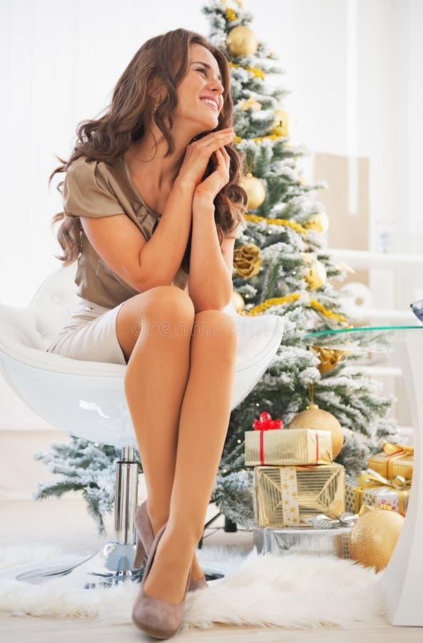 Πορτρέτο της στοχαστικής συνεδρίασης γυναικών μπροστά από το χριστουγεννιάτικο δέντρο στοκ φωτογραφίες