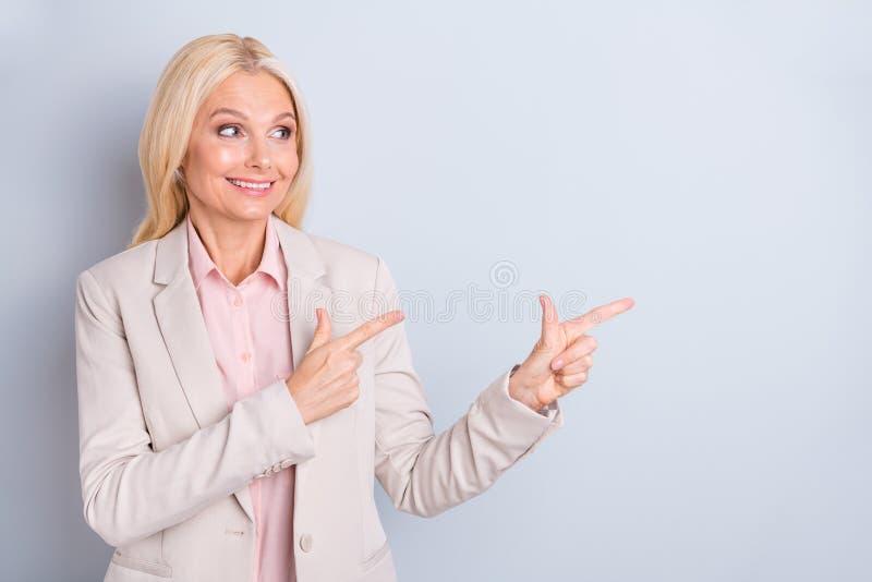 Πορτρέτο της συμπαθητική ελκυστική επιτυχής εύθυμη γκρίζος-μαλλιαρή κυρία που δείχνει δύο δείκτες αντιγράφει κατά μέρος τη διαστη στοκ εικόνα με δικαίωμα ελεύθερης χρήσης