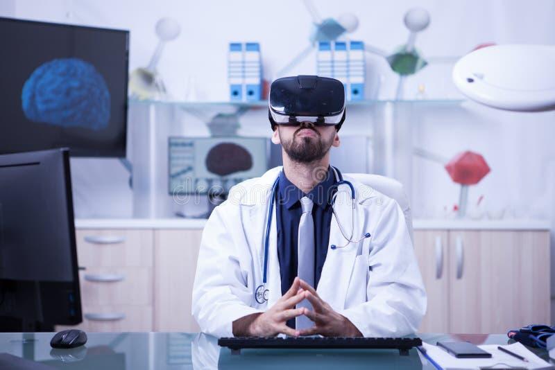 Πορτρέτο της συνεδρίασης γιατρών στο γραφείο του που χρησιμοποιεί το πιό headesτο να ανατρέξει εικονικής πραγματικότητας στοκ εικόνες